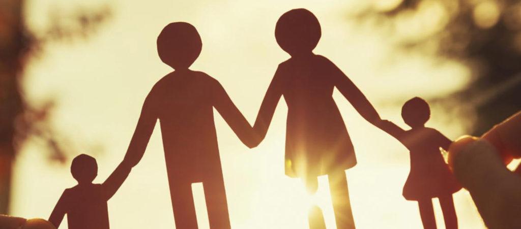 Семья из бумаги в руках человека