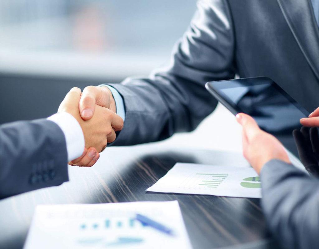 Рукопожатие двух бизнесменов в офисе США