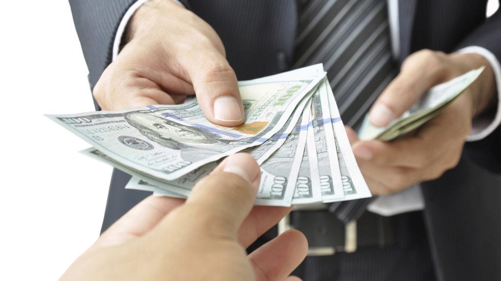 Бизнесмен дает деньги в долг другому человеку