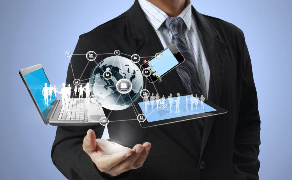 Бизнесмен держит в руке компьютер, планшет и телефон