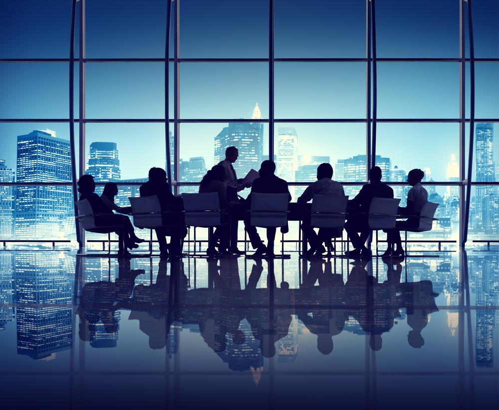 Команда сотрудников сидит за столом в американском офисе
