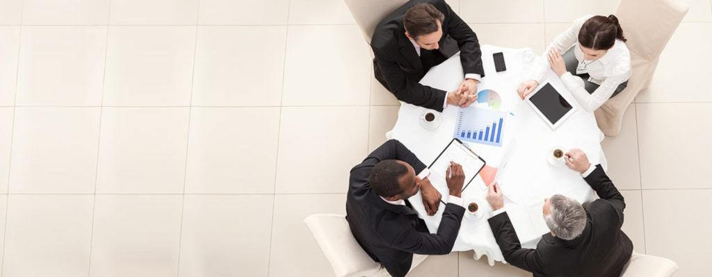 4 бизнесмена обсуждают бизнес проект за столом