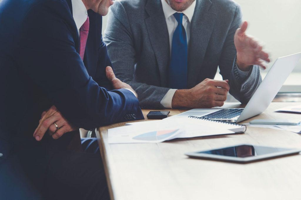 Бизнесмены обсуждают проект за столом с компьютером и планшетом
