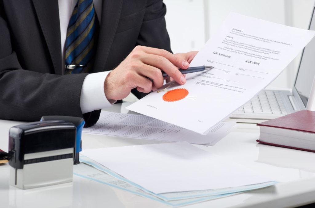 Бизнесмен держит в руках документ, подтверждающий сертификацию