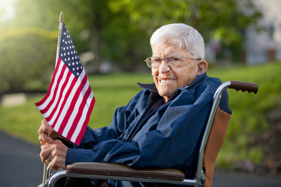Пожилой мужчина в инвалидном кресле держит в руках американский флаг