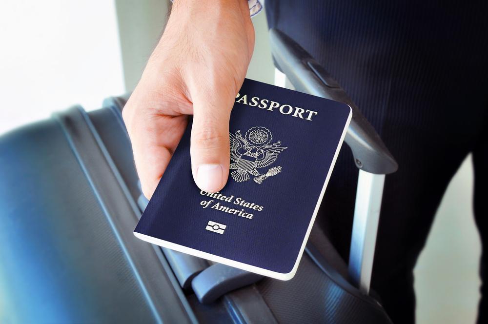 Американский паспорт в руке бизнесмена с чемоданом