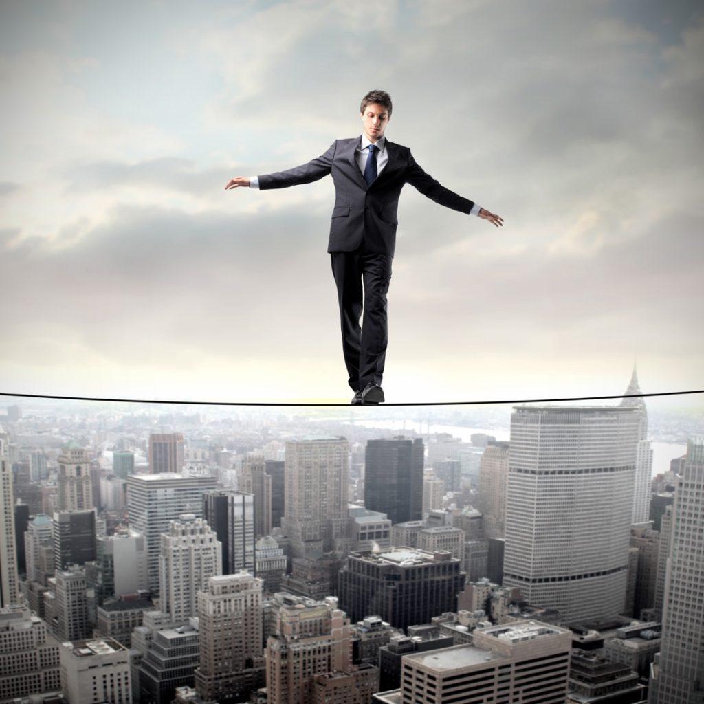 Бизнесмен балансирует на веревке над американским городом