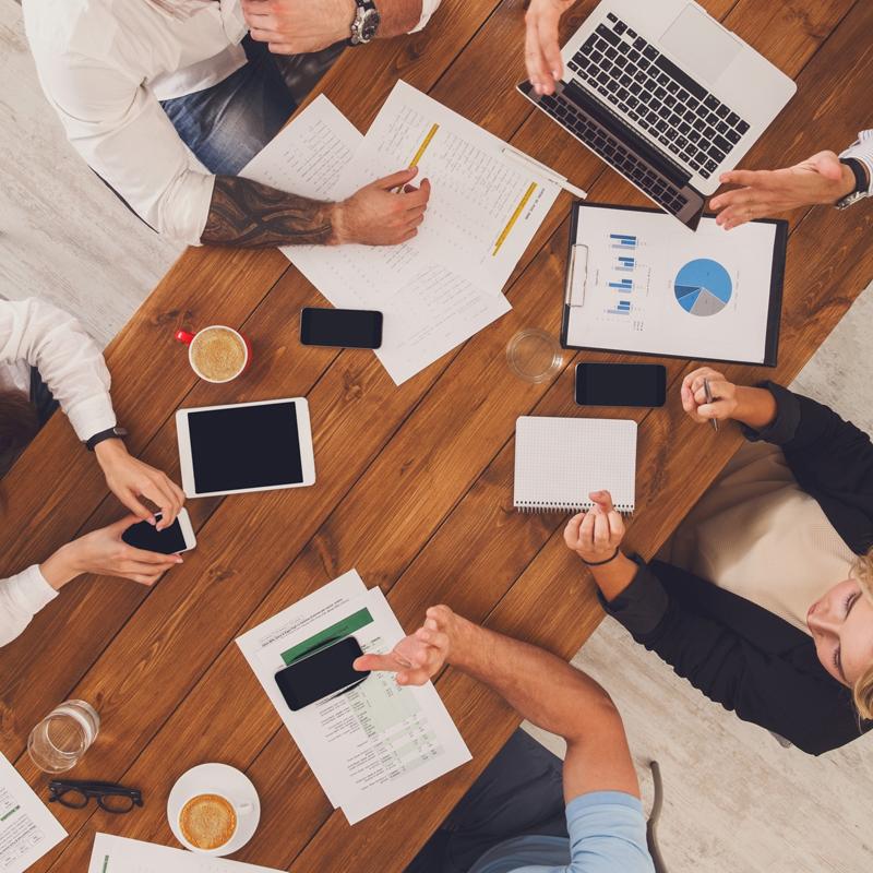 Сотрудники в офисе работают за столом с компьютером, планшетом, телефонами и документами