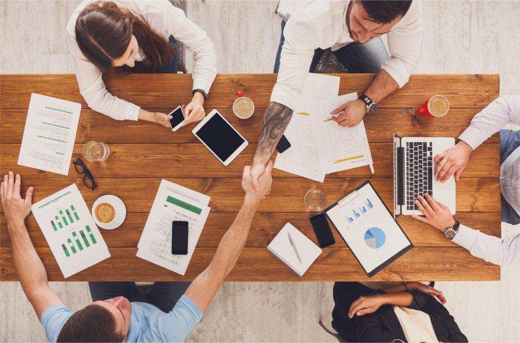Рукопожатие бизнесменов за столом с компьютером, планшетом и документами