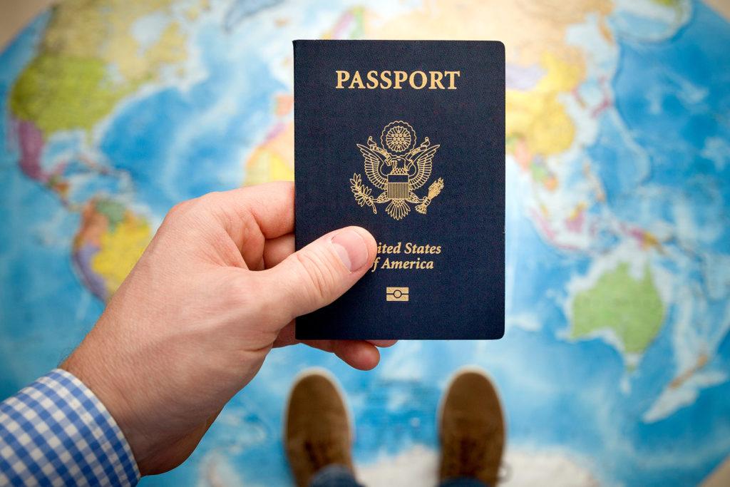 Американский паспорт в руке мужчины на фоне карты мира