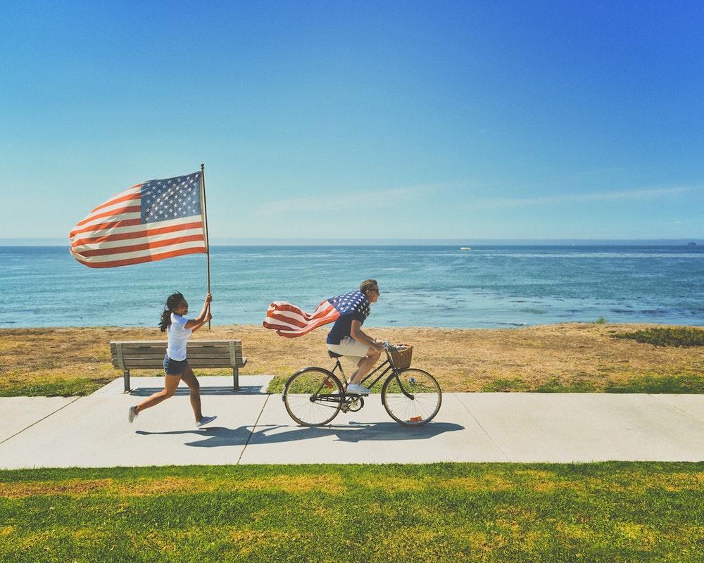 Мужчина на велосипеде и женщина с американским флагом в руках